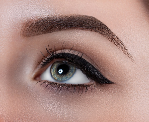Female eye close-up. Macro. Perfect makeup and eyebrows. Beautiful gray eyes