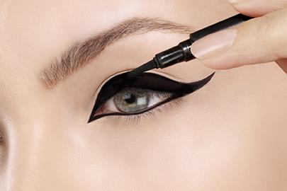 Beautiful model applying eyeliner closeup on eye