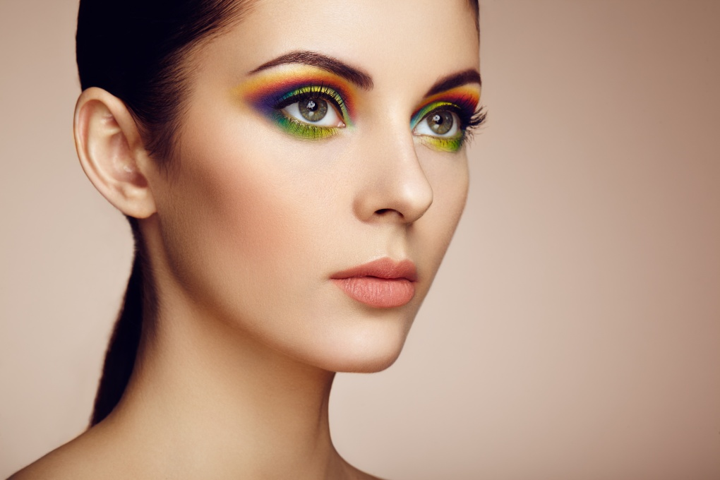 Portrait of beautiful young woman with rainbow make-up. Girl summer. Long eyelashes, vivid colorful eyeshadows. Multicolored